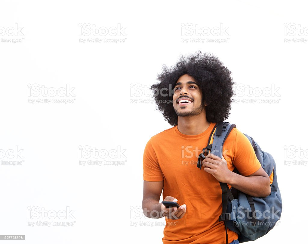 Happy guy walking with mobile phone and bag stock photo