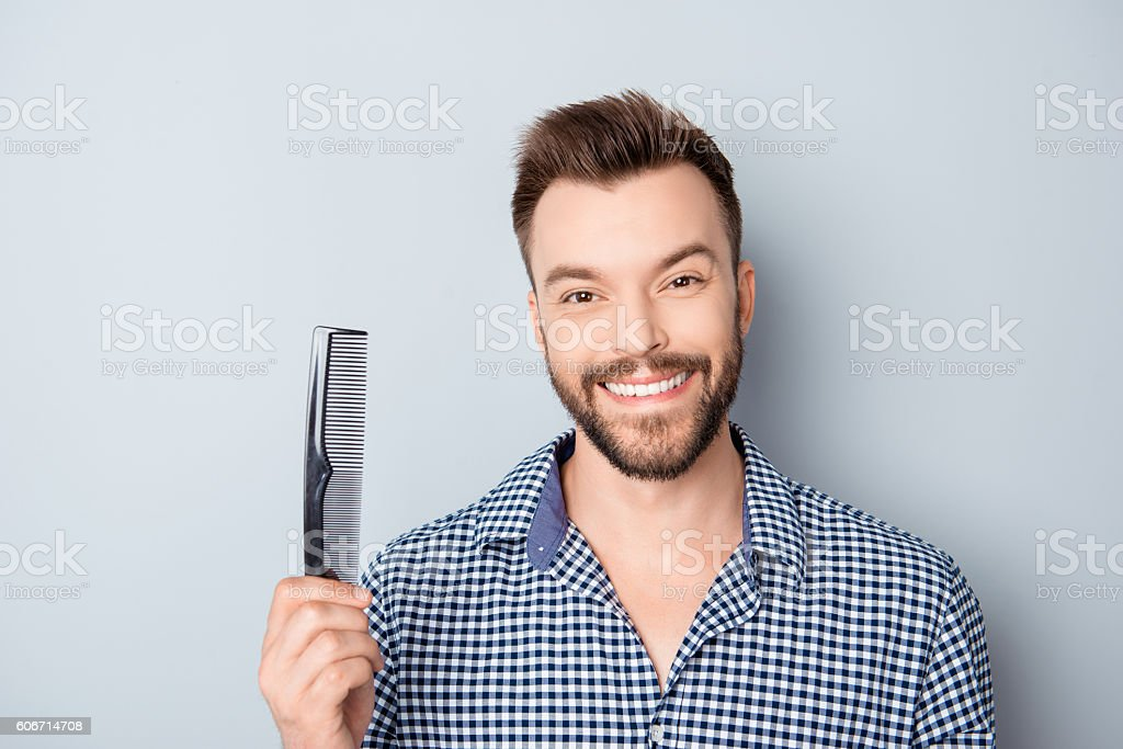 Happy guy with beaming smile and healthy hair holding comb stock photo