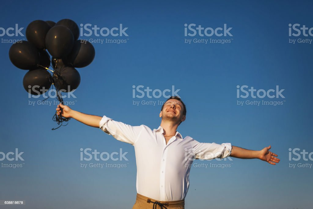 happy guy with black balloons reaches for the sky stock photo