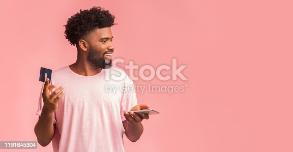 1173546354 istock photo Happy guy with smartphone recommending credit card 1191645304