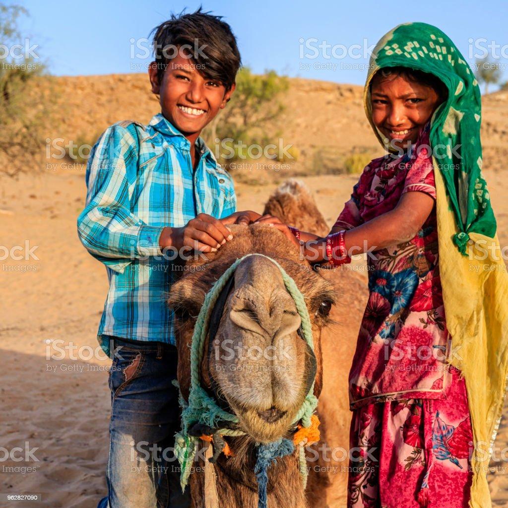 Happy Gypsy Indian children with camel, desert village, India - Foto stock royalty-free di Adolescente