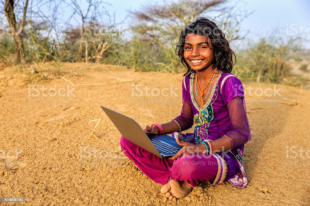 Happy Gypsy Indian young girl using laptop, India stock photo