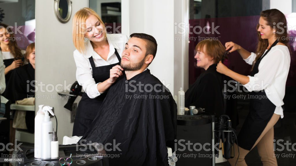 Happy hairdresser doing hairstyle - foto stock
