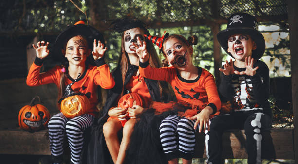 happy Halloween! a group of children in suits and with pumpkins in forest happy Halloween! a group of children in suits and with pumpkins in the forest costume stock pictures, royalty-free photos & images