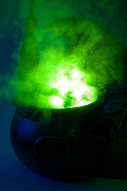 happy halloween, alchemie und zauber-trank-konzept mit einem topf oder kessel kochen eine grüne flüssigkeit dämpfe und rauch, neben einem besenstiel und eine hexe oder zauberer hut - pfannen test stock-fotos und bilder