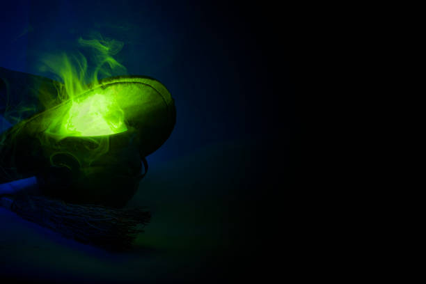 happy halloween, alchemie und zauber-trank-konzept mit einem topf oder kessel kochen eine grüne flüssigkeit dämpfe und rauch, neben einem besenstiel und eine hexe oder zauberer hut mit textfreiraum - pfannen test stock-fotos und bilder