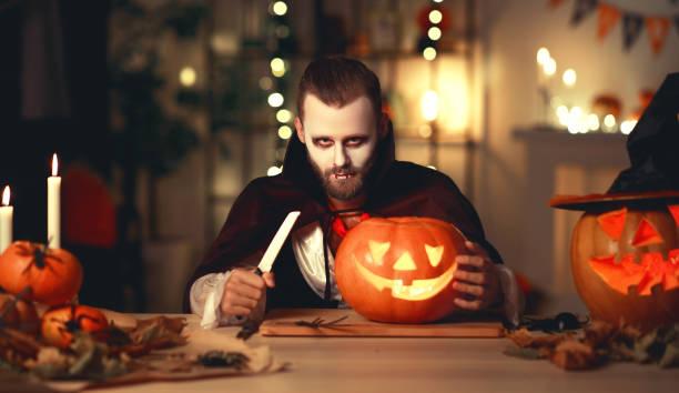 fröhliches halloween!  bärtiger mann in einem dracula vampirkostüm mit kürbis im dunklen haus - dracula schminken stock-fotos und bilder