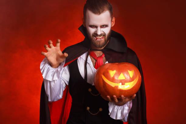 fröhliches halloween!  bärtiger mann in einem dracula vampirkostüm mit kürbis auf leuchtend rotem hintergrund - dracula schminken stock-fotos und bilder