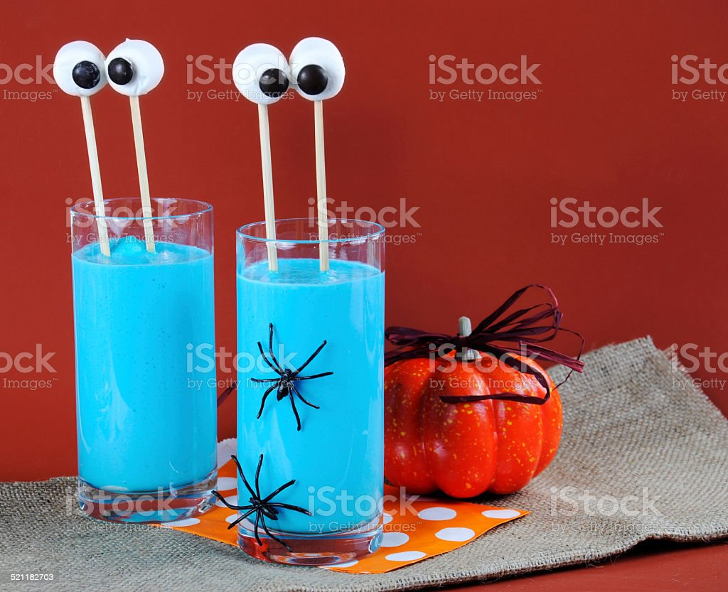 Happy Halloween blue smoothie drink with marshmallow eyes stock photo
