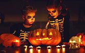 istock happy Halloween! children in costume of skeletons with pumpkins and candles in dark 1043855100