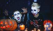 istock happy Halloween! children in costume of skeletons with pumpkins and candles in dark 1046471000