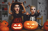 istock happy Halloween! children in costume of witch and skeletons with pumpkins and candles in dark 1043285298