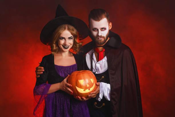 fröhliches halloween!  paar mann und frau in einem dracula vampir und hexe kostüme mit kürbis auf leuchtend roten hintergrund - dracula schminken stock-fotos und bilder