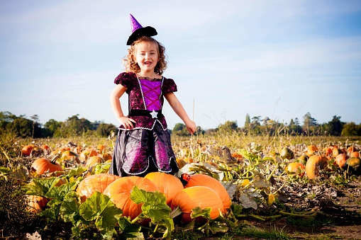 Happy Halloween! Cute cheerful little witch with a magic wand. Beautiful child girl in witch costume sitting on the big pumpkin, conjuring and laughing.