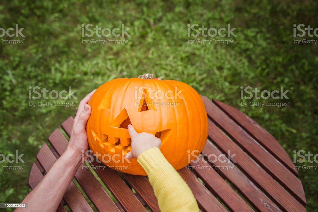 Happy Halloween Father And Small Daughters Look At The Face Cut In The Pumpkin High Angle View Small Giirl Show A Nose Of Pumpkin Jack O Lanterns Outside Stock Photo Download