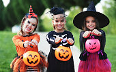 istock Happy Halloween! funny children in carnival costumes outdoors 1271018744