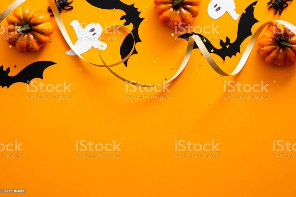 Happy halloween holiday concept. Halloween decorations, pumpkins, bats, ghosts on orange background. Halloween party greeting card mockup with copy space. Flat lay, top view, overhead. - Zbiór zdjęć royalty-free (Baner)