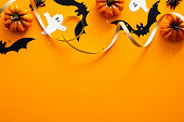 istock Happy halloween holiday concept. Halloween decorations, pumpkins, bats, ghosts on orange background. Halloween party greeting card mockup with copy space. Flat lay, top view, overhead. 1171184656