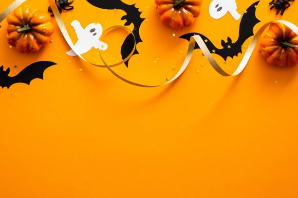 buon concetto di vacanza di halloween. decorazioni di halloween, zucche, pipistrelli, fantasmi su sfondo arancione. mockup del biglietto d'auguri per feste di halloween con spazio di copia. lay piatto, vista dall'alto, sopra la testa. - halloween foto e immagini stock