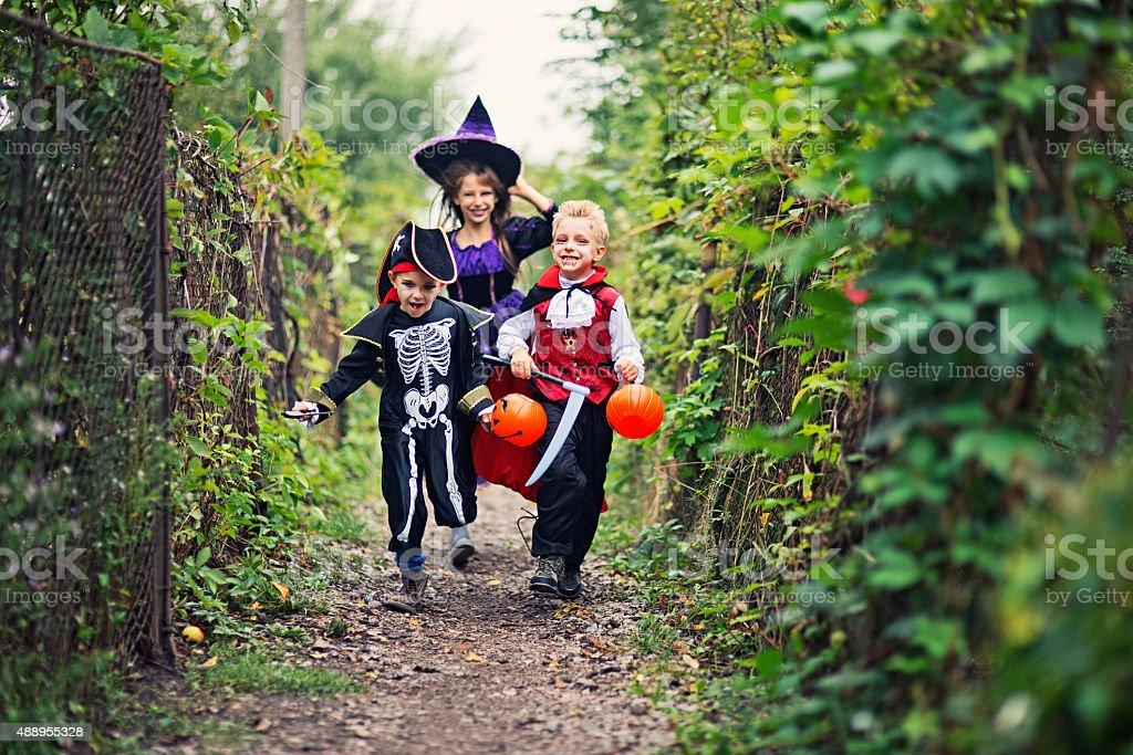 Happy halloween kids running on a path stock photo