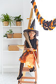 istock Happy Halloween. little beautiful girl in a witch costume celebrates a home in an interior with pumpkins 1167528730
