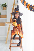 istock Happy Halloween. little beautiful girl in a witch costume celebrates a home in an interior with pumpkins 1167528755