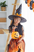 istock Happy Halloween. little beautiful girl in a witch costume celebrates a home in an interior with pumpkins 1167528758