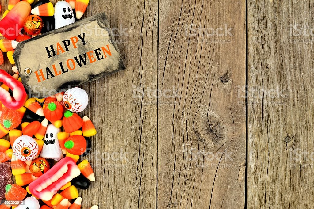 Happy Halloween tag with candy side border over rustic wood stock photo