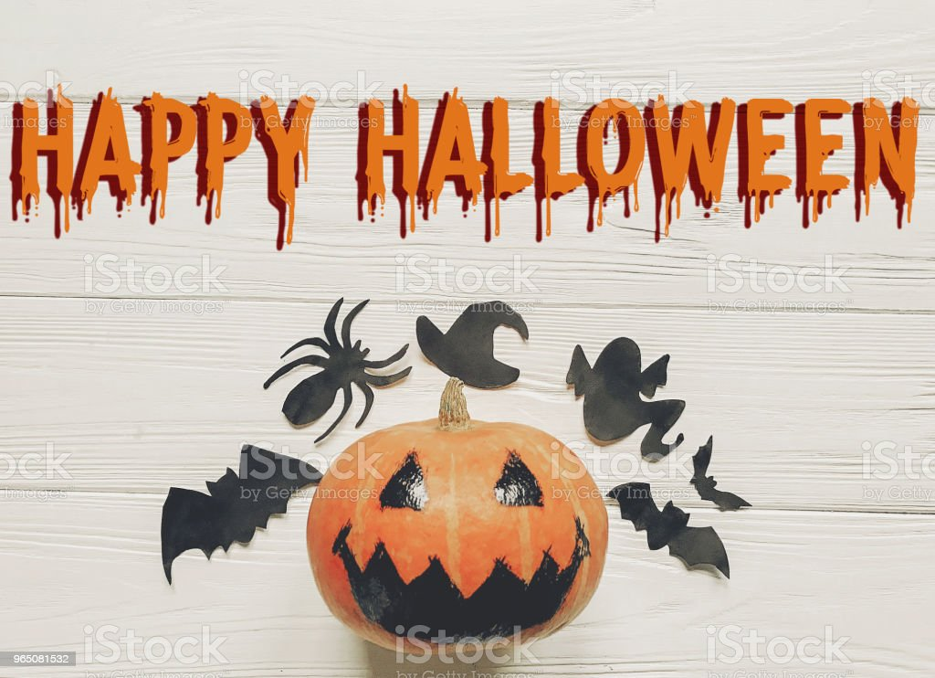 happy halloween text flat lay. jack lantern pumpkin with witch ghost bats and spider black decorations on white wooden background top view, space for text. seasonal greetings. zbiór zdjęć royalty-free