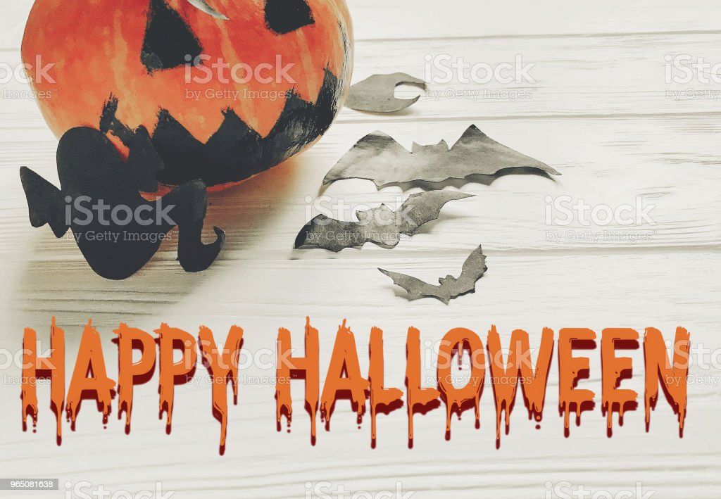 happy halloween text. jack lantern pumpkin with witch ghost bats and spider black decorations on white wooden background. simple cutouts for autumn holiday celebration. seasonal greetings royalty-free stock photo