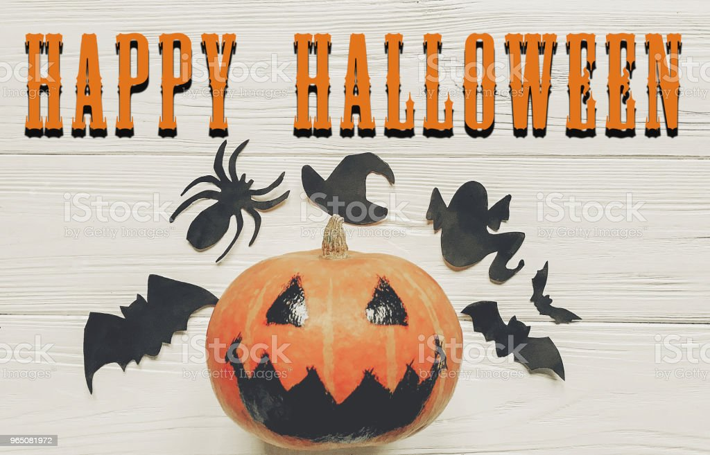 happy halloween text. jack lantern pumpkin with witch ghost bats and spider black decorations on white wooden background. simple cutouts for autumn holiday celebration. zbiór zdjęć royalty-free