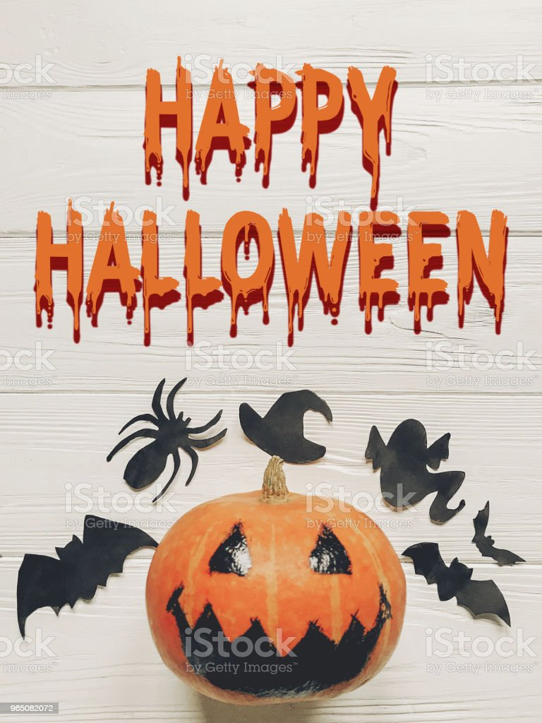 happy halloween text. jack lantern pumpkin with witch ghost bats and spider black decorations on white wooden background top view. seasonal greetings, space text zbiór zdjęć royalty-free