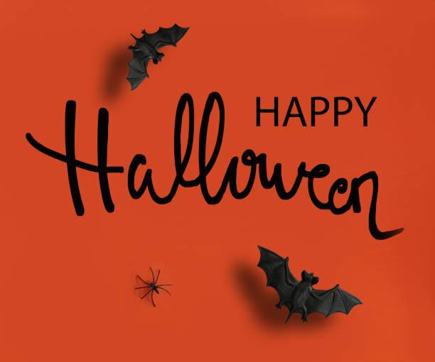 happy halloween text auf orangefarbenem hintergrund - handschriftliche typografie stock-fotos und bilder