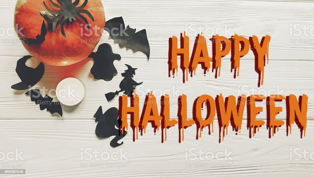 happy halloween text. pumpkin with witch ghost bats and spider black decorations on white wooden background top view with space for text. seasonal greetings, holiday celebration royalty-free stock photo