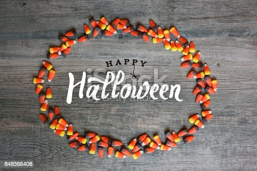 1057069236 istock photo Happy Halloween Typography With Candy Corn Oval Frame Over Wooden Background 848366408