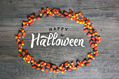 istock Happy Halloween Typography With Candy Corn Oval Frame Over Wooden Background 848366408
