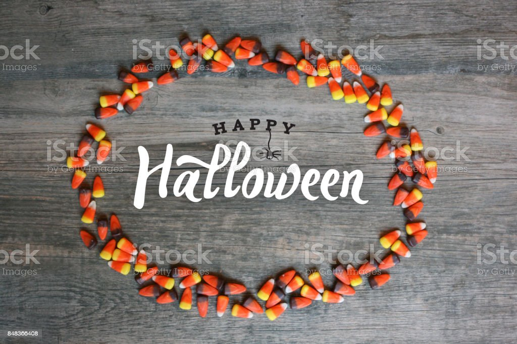 Happy Halloween Typography With Candy Corn Oval Frame Over Wooden Background stock photo