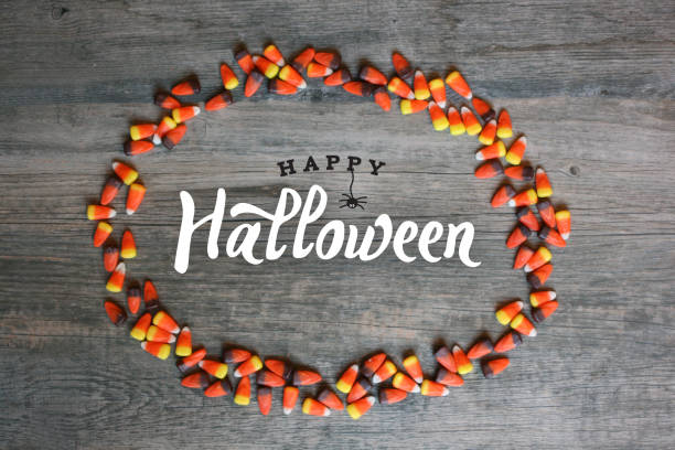 happy halloween typography with candy corn oval frame over wooden background - halloween стоковые фото и изображения