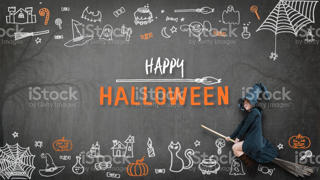 Happy halloween with girl kid in witch costume riding broomstick on spooky dark black chalkboard with chalk doodle of trick or treat candies and scary ghost for holiday greeting festival celebration stock photo