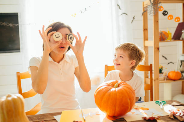 Happy halloween. Young beautiful mother and her son carving pumpkin. Happy family preparing for Halloween. Happy Halloween concept stock photo
