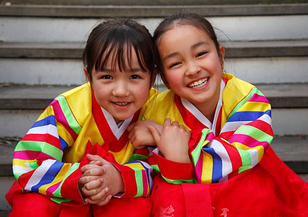 Happy Hanbok - two young girls in colorful dresses smiling stock photo