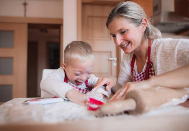 屋内で焼く母親と一緒に幸せな障害ダウン症の子。 - disabilitycollection ストックフォトと画像