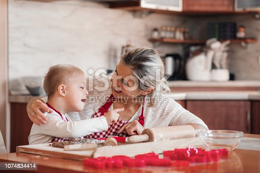 istock A happy handicapped down syndrome child with his mother indoors baking. 1074834414