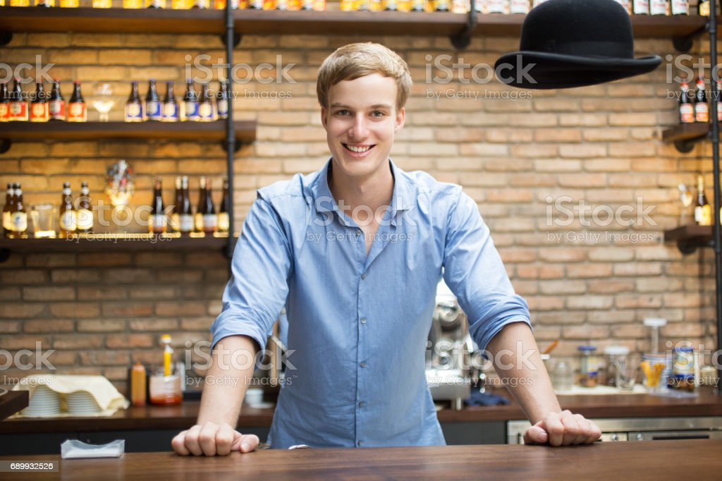 Happy Handsome Blond Bartender Standing at Counter stock photo