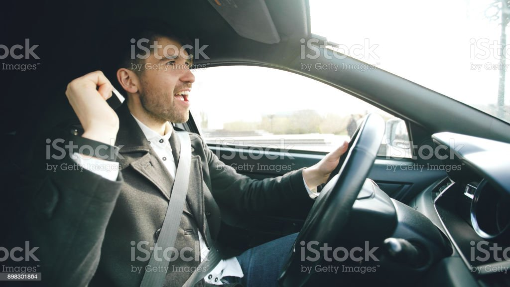 Happy handsome businessman driving car and singing. Man is happy after making deals and drives home stock photo