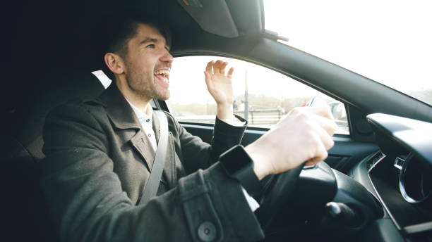 Happy handsome businessman driving car and singing. Man is happy after making deals and drives home Happy handsome businessman driving car and singing. Man is happy after making deals and drive home singing stock pictures, royalty-free photos & images