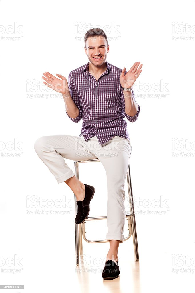 Happy handsome gay sitting on bar stool and waving hands stock photo