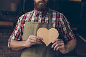 istock Happy handsome joiner in love holding and showing handmade wooden heart. He love his job 944597260