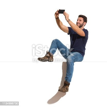 istock Happy Handsome Man Is Sitting Relaxed On A Top And Taking A Selfie 1134998730