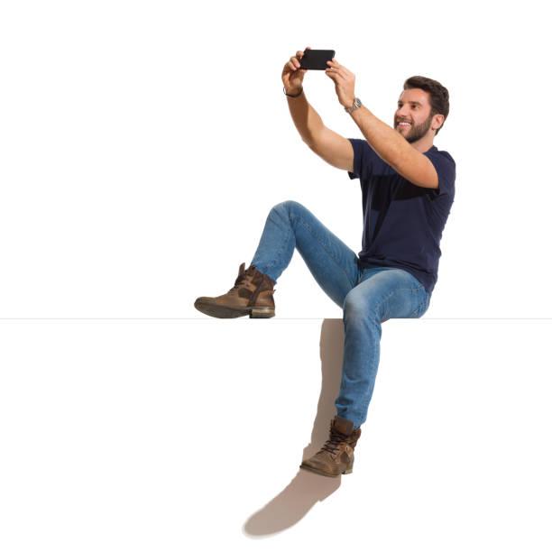 hombre guapo feliz está sentado relajado en una parte superior y tomar un selfie - sentado fotografías e imágenes de stock
